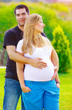 Young couple awaiting baby. Husband take care about his pregnant wife, walking in spring park, loving family, new life concept Royalty Free Stock Images