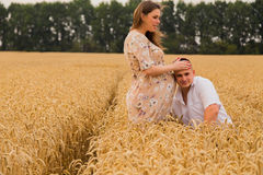 Young couple awaiting baby among the wheat field. A men and a women in tender embrace. Sincere feelings and true love. Photos for magazines, posters and Royalty Free Stock Photography