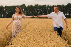 Young couple awaiting baby among the wheat field. A men and a women in tender embrace. Sincere feelings and true love. Photos for magazines, posters and Royalty Free Stock Photo