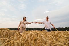 Young couple awaiting baby among the wheat field. A men and a women in tender embrace. Sincere feelings and true love. Photos for magazines, posters and Stock Photography