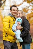 Young couple with baby boy in autumn park Stock Photo
