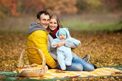 Young couple with baby boy on picnic. In autumn park Stock Photo
