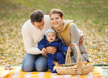 Young couple with baby boy on picnic in autumn. Park Stock Photos