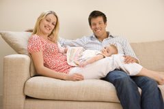 Young couple with baby girl (9-12 months), sitting on sofa, smiling, portrait Stock Image