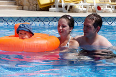 A young couple and baby in a pool Royalty Free Stock Photo