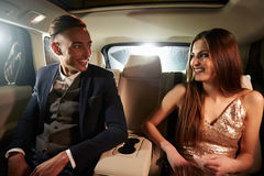 Young couple in the back of a limo looking at each other Stock Images