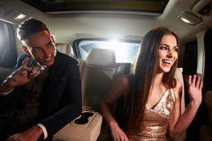 Young couple in the back of a limo looking out of the window Stock Photos