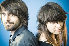 Young Couple Back-to-Back. A studio portrait of a young couple standing back-to-back with a blue background stock photo