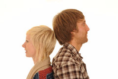 Young couple back to back. Portrait of young auburn haired man and blond woman back to back, white background Stock Photos