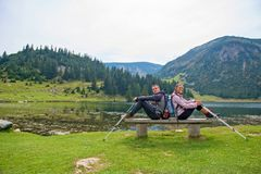 Young couple of backpackers near the lake in mountains.  royalty free stock photo