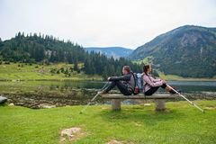 Young couple of backpackers near the lake in mountains.  stock photo