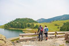 Young couple of backpackers near the lake in mountains.  stock photography