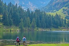 Young couple of backpackers near the lake in mountains.  stock image