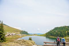 Young couple of backpackers near the lake in mountains.  royalty free stock image
