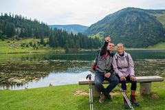Young couple of backpackers near the lake in mountains.  royalty free stock images