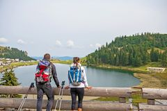 Young couple of backpackers near the lake in mountains.  royalty free stock photography