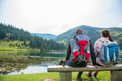 Young couple of backpackers near the lake in mountains.  stock images