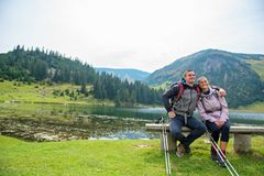 Young couple of backpackers near the lake in mountains.  royalty free stock photos