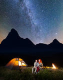 Young couple backpackers sitting together under starry sky near campfire and shines tent at night Stock Photos