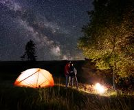 Young couple standing hugging each other by fire and trees under night sky with bright stars. Young couple backpackers standing hugging each other by the fire Royalty Free Stock Image