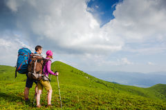 Young couple with backpacks hiking in the mountains. And enjoying valley view stock images