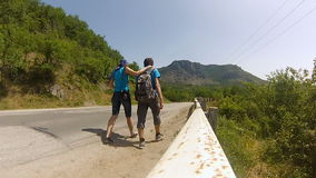 Young couple with backpacks walking along the road in the mountains. Of the Crimea in the summer stock video