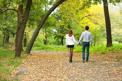 Young couple backside in autumn park Royalty Free Stock Photography