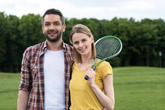 Young couple with badminton racquet standing together in park Royalty Free Stock Photos