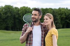 Young couple with badminton racquet standing together in park Royalty Free Stock Images