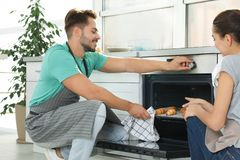 Young couple baking croissants in oven royalty free stock photo