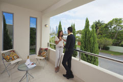 Young couple on balcony. Young couple toasting with champagne on a modern balcony overlooking the city Royalty Free Stock Images