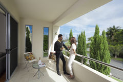 Young couple on balcony. Young couple toasting with champagne on a modern backyard overlooking the city Royalty Free Stock Images