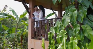 Young couple on balcony in tropical forest stnd embracing use cell smart phone surfing internet together happy man and. Woman slow motion 60 stock video footage