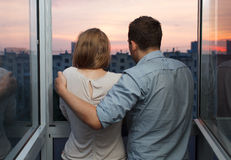 Young couple on the balcony watching sunset. Young couple on the balcony at a high floor looking at city during sunset Royalty Free Stock Images