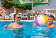 Young Couple with Ball in Resort Swimming Pool Stock Photos
