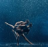 Young couple of ballet dancers dancing unde rwater drops. Young couple of ballet dancers dancing under water splash and drops. Young caucasian and afro american Stock Photo