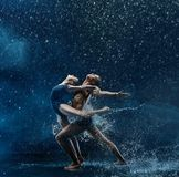 Young couple of ballet dancers dancing unde rwater drops stock photography