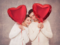 Young couple with balloons in the form of heart Royalty Free Stock Images