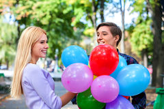 Young couple with balloons in the park. Royalty Free Stock Photography