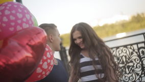 Young couple with balloons walking on the promenade stock video