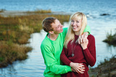 Young couple on banks of river Stock Photography