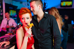 Young couple in bar or club drinking cocktails Royalty Free Stock Image