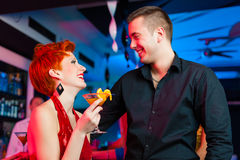 Young couple in bar or club drinking cocktails Royalty Free Stock Images