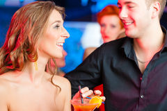Young couple in bar or club drinking cocktails stock photography