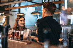 Young couple at bar with different craft beers Royalty Free Stock Photos