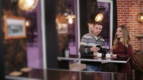 Young couple at the bar drinking coffee and having a conversation. Beautiful couple at the bar in a cafe drinking coffee and talking stock video footage