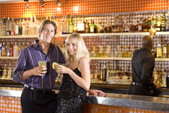 Young couple at bar with drinks, smiling, portrait Stock Photography