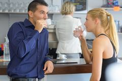 Young couple at bar having coffee and flirting Royalty Free Stock Images