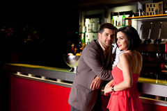 Young couple in bar talking. Young couple bar counter having drinks Royalty Free Stock Photography