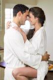 Young couple in bathrobe cuddling each other Stock Photos